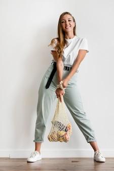 Frau, die einen recycelbaren beutel mit gesundem essen hält