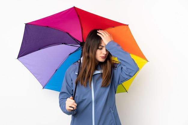 Frau, die einen regenschirm auf weißer wand hält, die zweifel mit verwirrendem gesichtsausdruck hat
