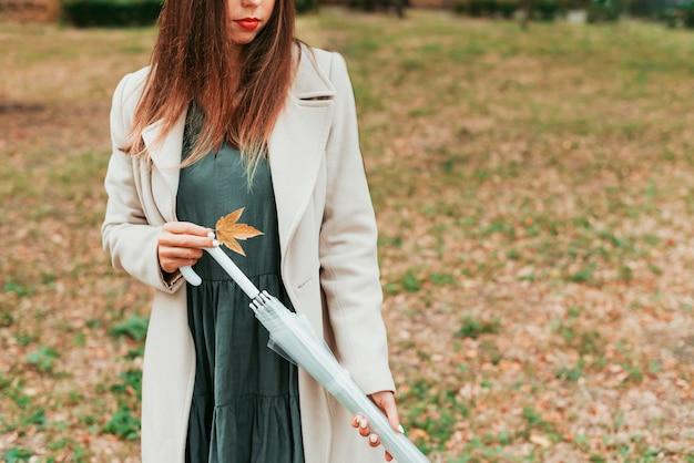 Frau, die einen regenschirm im herbst hält