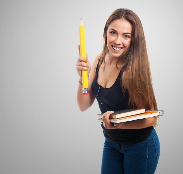 Frau, die einen riesigen bleistift und ein notebook