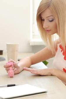 Frau, die einen rosa lack verwendet