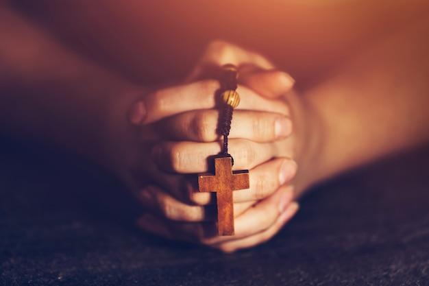 Frau, die einen rosenkranz hält und betet