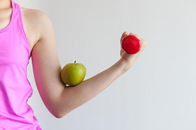 Frau, die einen roten dummkopf für übung und training, grünen apfel auf arm für gesundes leben hält