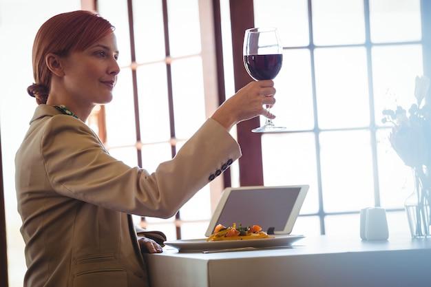Frau, die einen rotwein hält