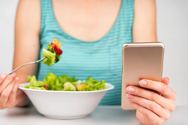 Frau, die einen salat isst und telefon betrachtet