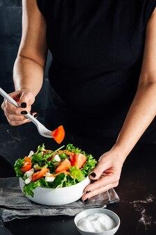 Frau, die einen salat mit tomaten-salat-olivenöl und salzkonzept der gesunden diät vorbereitet