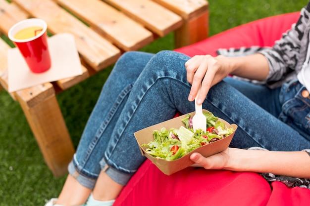 Frau, die einen salat und eine gabel hält