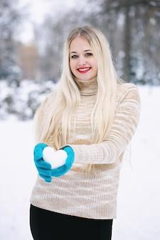 Frau, die einen schneeball in der form eines herzens hält