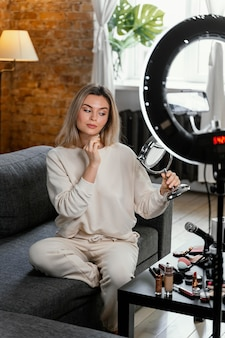 Frau, die einen schönheits-vlog zu hause tut Kostenlose Fotos