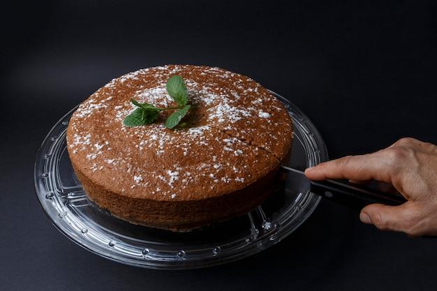 Frau, die einen schokoladenkuchen mit zuckerdekoration mit einem messer schneidet