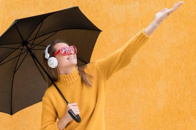 Frau, die einen schwarzen regenschirm hält, während sie ihre hand erhebt