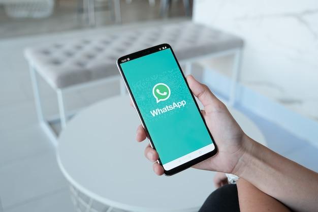 Frau, die einen smartphone und einen offenen appstore sucht sozialinternet-service whatsapp auf dem schirm hält.