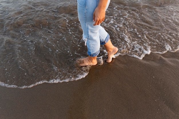 Frau, die einen spaziergang auf dem strand im wasser nimmt