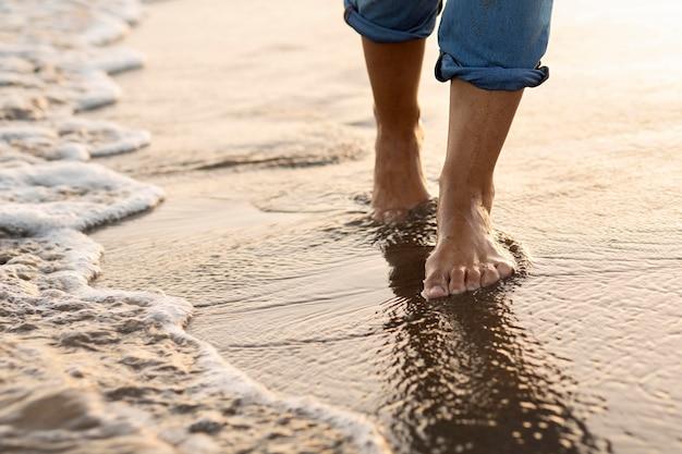 Frau, die einen spaziergang auf dem strandsand nimmt