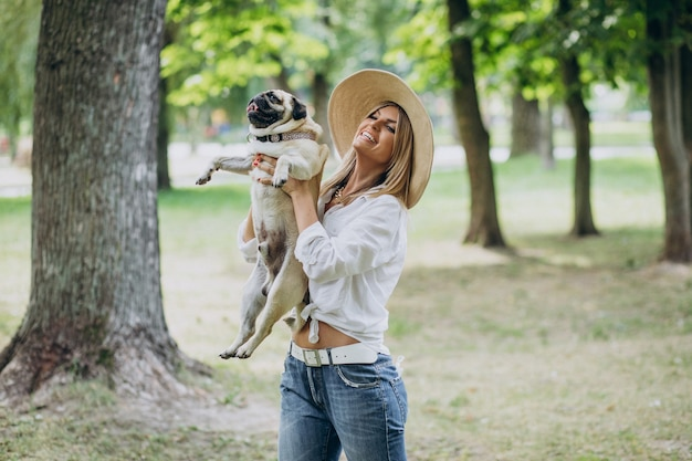 Frau, die einen spaziergang im park mit ihrem mops-haustier hat
