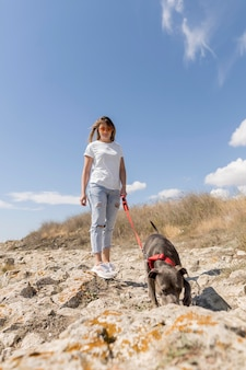 Frau, die einen spaziergang mit ihrem hund am strand macht