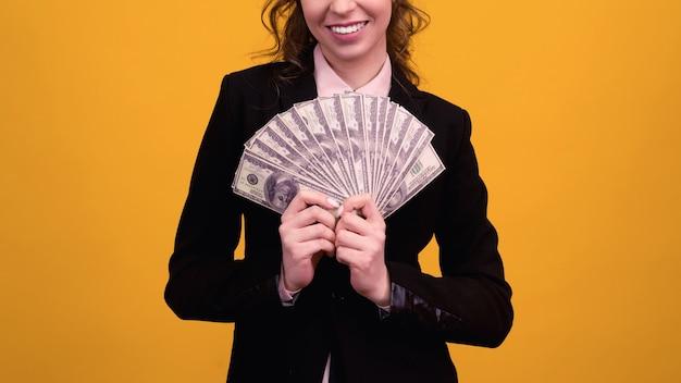Frau, die einen stapel geld lokalisiert auf gelb zeigt.