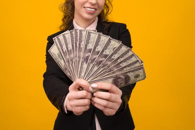 Frau, die einen stapel geld mit ihrem finger lokalisiert auf gelbem hintergrund zeigt.