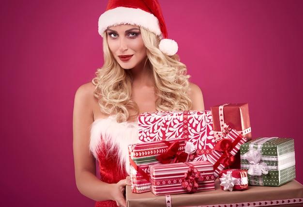 Frau, die einen stapel geschenke trägt