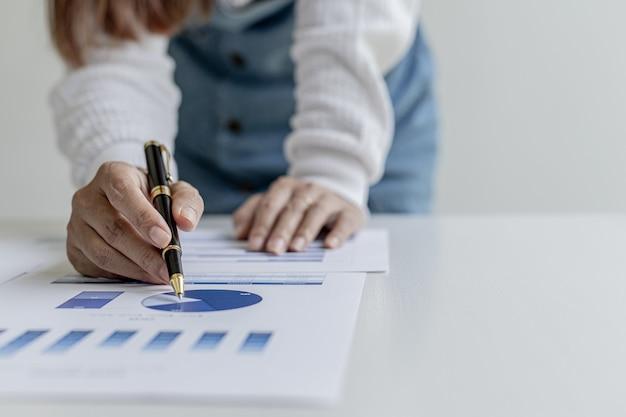 Frau, die einen stift hält, der auf dokumente auf einem schreibtisch zeigt, sie ist finanzwissenschaftlerin, sie überprüft die finanzdokumente des unternehmens auf richtigkeit, bevor sie sie den führungskräften präsentiert. konzept der finanzprüfung.