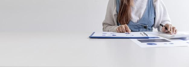 Frau, die einen stift hält, der auf ein dokument auf ihrem schreibtisch zeigt und einen taschenrechner drückt, überprüft die zahlen auf den von der finanzabteilung vorbereiteten finanzdokumenten. konzept der finanzprüfung.
