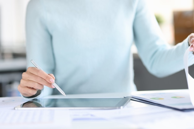 Frau, die einen stift mit der hand über einem tablet hält und seite in dokumenten nahaufnahme umblättert
