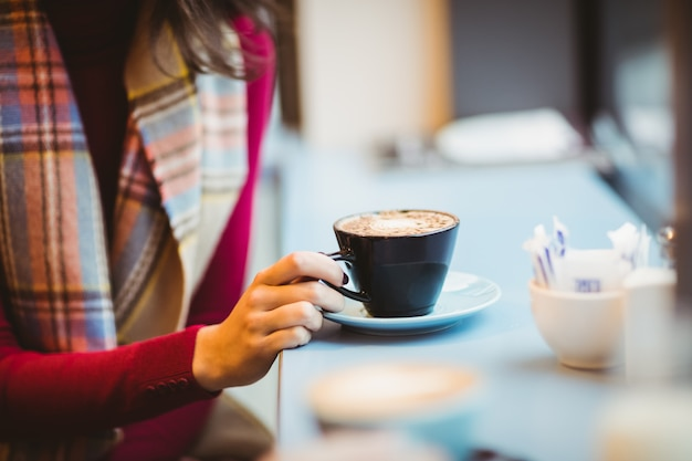 Frau, die einen tasse kaffee hält