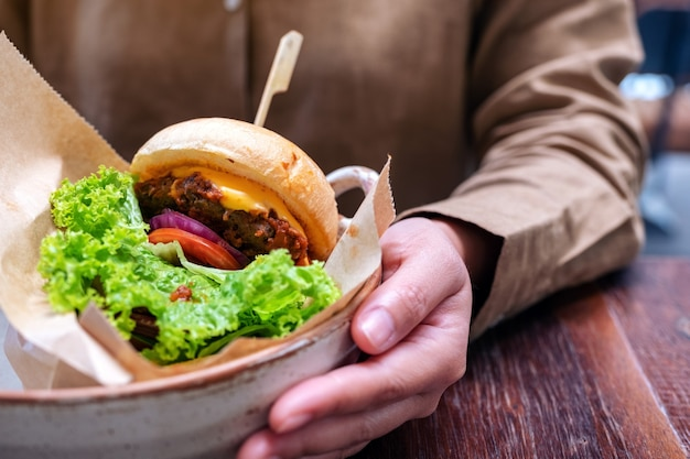 Frau, die einen teller rindfleischhamburger auf holztisch im restaurant hält
