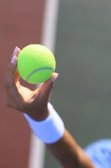 Frau, die einen tennisball mit tennisplatz im hintergrund hält.
