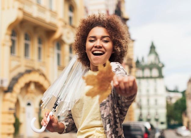 Frau, die einen transparenten regenschirm im herbst hält