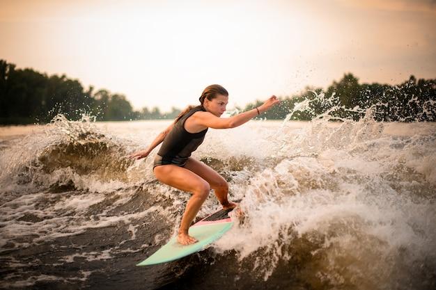 Frau, die einen trick auf dem grünen wakeboard auf dem fluss im sonnenuntergang macht