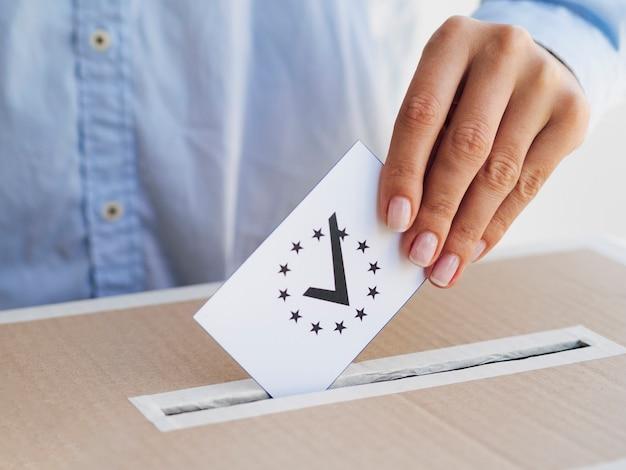Frau, die einen überprüften europäischen stimmzettel in kasten einsetzt