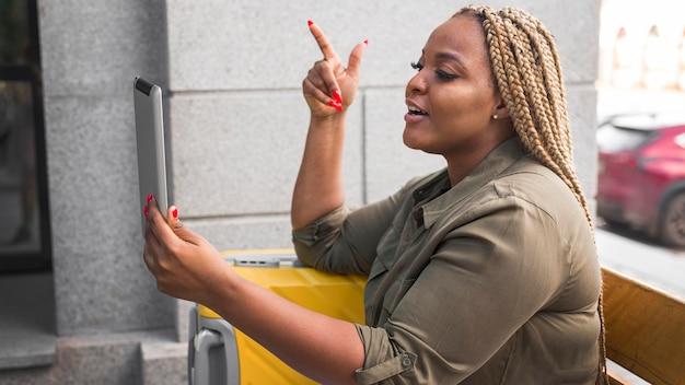Frau, die einen videoanruf auf ihrem tablett während der reise hat