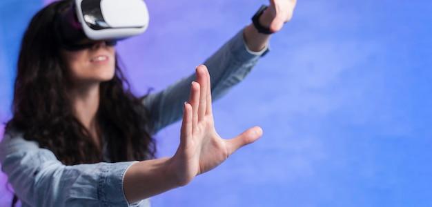 Frau, die einen vr satz trägt und hände in der luft hält