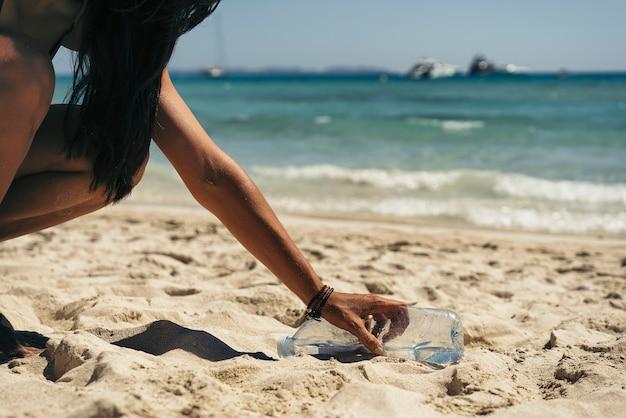 Frau, die einen wasserflaschenmüll vom strand aufhebt.