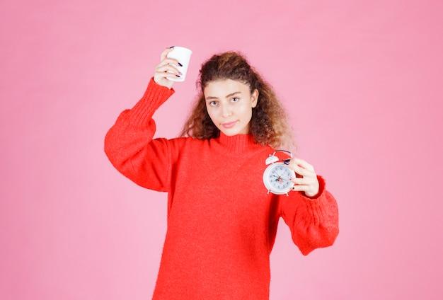 Frau, die einen wecker und eine tasse kaffee hält und auf ihre morgenroutine zeigt.