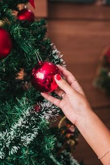 Frau, die einen weihnachtsbaum schmückt