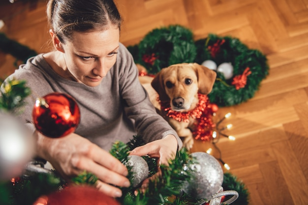 Frau, die einen weihnachtsbaum verziert