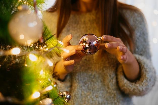 Frau, die einen weihnachtsbaumball hält