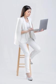 Frau, die einen weißen anzug trägt, der sitzt und durch den computer arbeitet, isoliert auf weißem hintergrund