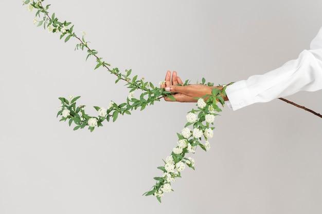 Frau, die einen zweig der schneeweidenblume hält