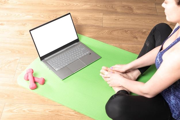 Frau, die einige meditation und yoga zu hause in einem laptop-computer mit modell weißen leeren bildschirm praktiziert