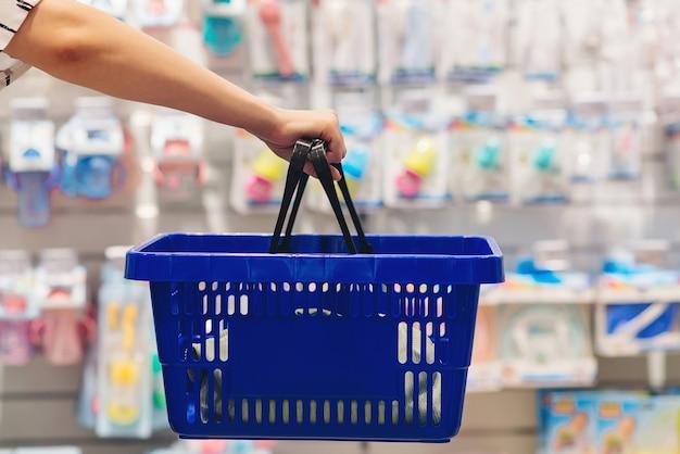 Frau, die einkaufskorb hält. mama wählt neugeborenes babyprodukt im supermarkt schwangerschaft und einkaufen. frau, die babysachen im babyshop wählt.