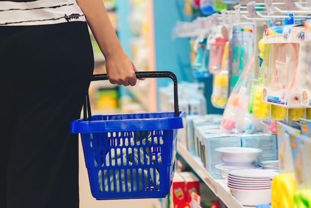 Frau, die einkaufskorb hält. mama wählt neugeborenes babyprodukt im supermarkt