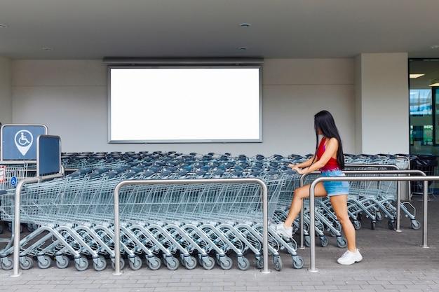 Frau, die einkaufslaufkatze im parkplatz für warenkörbe wählt