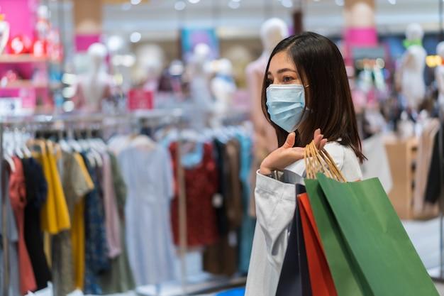 Frau, die einkaufstasche hält und auf kleidung im einkaufszentrum schaut und medizinische maske zur verhinderung von coronavirus trägt