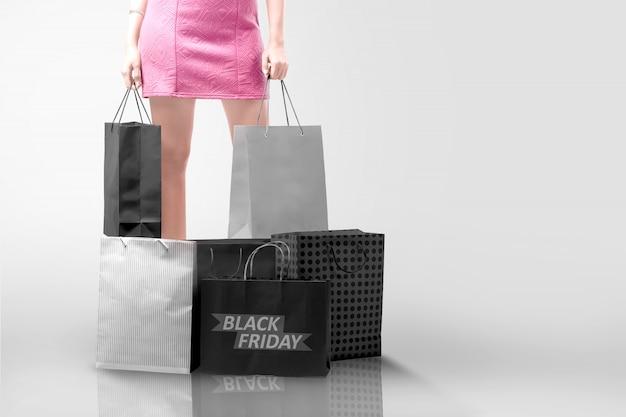 Frau, die einkaufstasche mit einem stapel einer einkaufstasche mit black friday-text hält