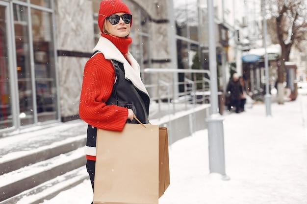 Frau, die einkaufstaschen an einem außeneinkaufszentrum trägt