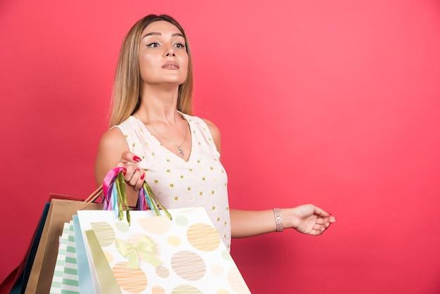 Frau, die einkaufstaschen beim schauen trägt.