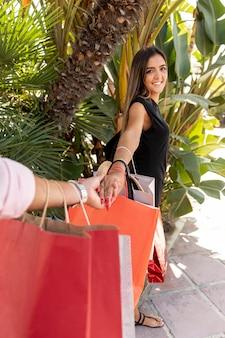 Frau, die einkaufstaschen hält und kamera betrachtet